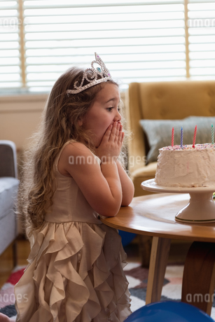 Surprised girl looking at her birthday cakeの写真素材 [FYI02244593]