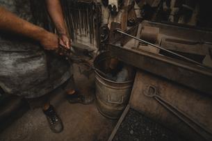 Blacksmith dipping hot metal rod in waterの写真素材 [FYI02244676]