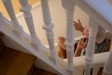 Senior man talking on mobile phone on stairsの写真素材 [FYI02244729]