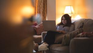 Female vlogger sitting on sofa while using laptopの写真素材 [FYI02244773]