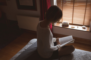 Woman reading book on bed in bedroomの写真素材 [FYI02244823]