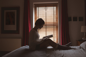 Woman reading book on bed in bedroomの写真素材 [FYI02244832]