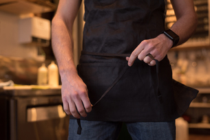 Male waiter wearing apron in cafeの写真素材 [FYI02244844]
