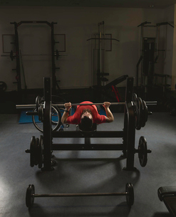 Handicapped man doing barbell bench pressing while exercisingの写真素材 [FYI02244863]