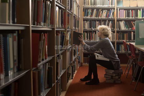 Woman removing a book from bookshelf in libraryの写真素材 [FYI02244886]