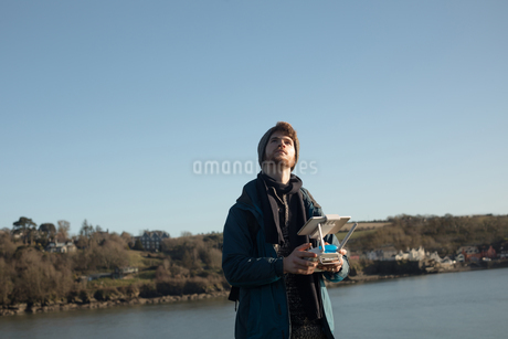 Male hiker operating drone near lakeの写真素材 [FYI02244890]