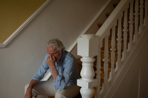 Senior man sitting on stairs at homeの写真素材 [FYI02244923]