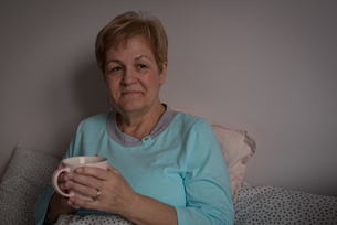 Senior woman having coffee in bedroomの写真素材 [FYI02244924]