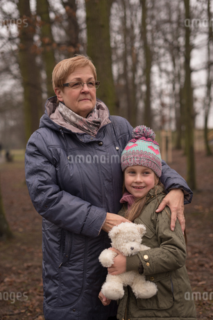 Grandmother and granddaughter standing in forestの写真素材 [FYI02244940]