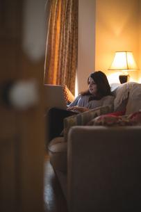 Female vlogger sitting on sofa while using laptopの写真素材 [FYI02244950]