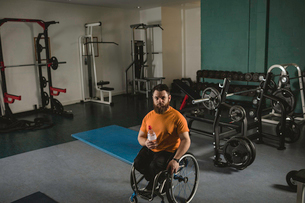 Handicapped man on wheelchair with water bottle in gymの写真素材 [FYI02244983]