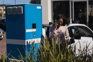 Woman talking on mobile phone while charging electric carの写真素材 [FYI02244992]