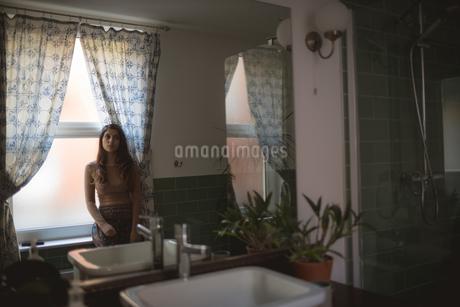 Woman sitting on window sill in bathroomの写真素材 [FYI02245023]