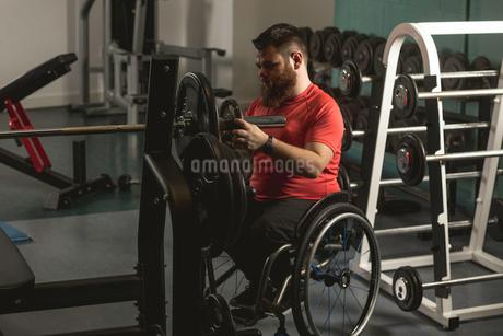 Handicapped man adjusting barbellの写真素材 [FYI02245027]