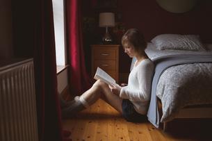 Beautiful woman reading book in bedroomの写真素材 [FYI02245070]