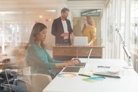 Female graphic designer using laptop at deskの写真素材 [FYI02245097]