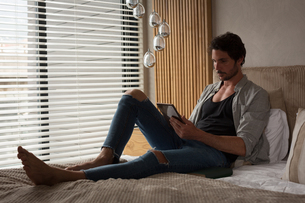 Man using digital tablet in bedroomの写真素材 [FYI02245115]