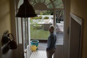 Senior man standing near door at homeの写真素材 [FYI02245132]