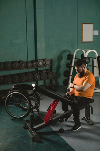 Handicapped man using mobile phone on bench pressの写真素材 [FYI02245145]