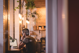 Man using laptop in cafeの写真素材 [FYI02245154]