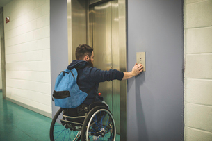 Handicapped man pressing button of elevatorの写真素材 [FYI02245166]