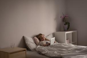 Girl using digital tablet in bedroomの写真素材 [FYI02245176]