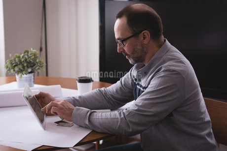 Male executive using digital tablet at deskの写真素材 [FYI02245184]