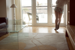 Woman looking through window at homeの写真素材 [FYI02245198]
