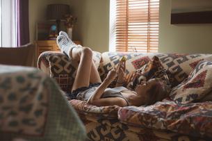 Woman using mobile phone while lying on sofaの写真素材 [FYI02245228]