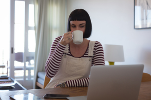 Woman having coffee while using laptop at homeの写真素材 [FYI02245274]