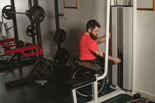 Handicapped man on wheelchair increasing weight of pulldown exerciseの写真素材 [FYI02245277]