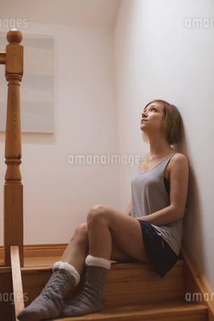 Thoughtful beautiful woman sitting on staircaseの写真素材 [FYI02245298]