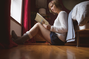 Beautiful woman reading book in bedroomの写真素材 [FYI02245301]