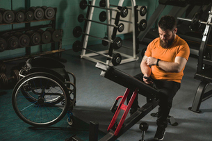 Handicapped man using mobile phone on bench pressの写真素材 [FYI02245326]