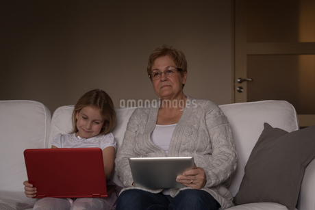 Grandmother and granddaughter using laptop and digital tabletの写真素材 [FYI02245328]