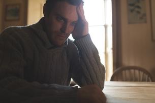 Depressed man relaxing at homeの写真素材 [FYI02245338]