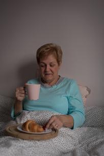 Senior woman having coffee and breakfast in bedroomの写真素材 [FYI02245343]