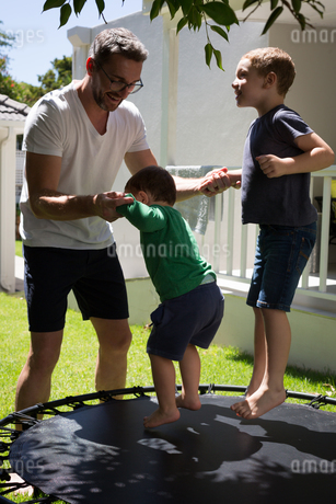 Father playing with his sons in gardenの写真素材 [FYI02245370]
