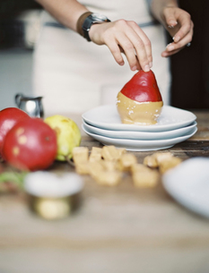 Dipping fresh organic pears into a sauce for dessert.の写真素材 [FYI02245437]