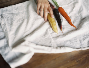 A person arranging fresh carrots on a white cloth.の写真素材 [FYI02245439]