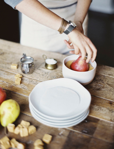 Dipping fresh organic pears into a sauce for dessertの写真素材 [FYI02245451]