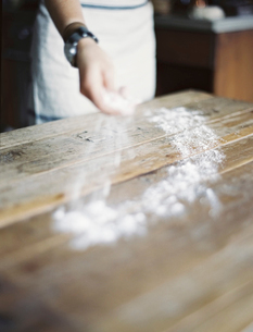 A woman cooking. Spreading flour across a tabletop.の写真素材 [FYI02245467]