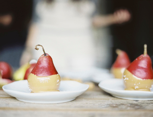 Fresh organic pears dipped into a sauce for dessertの写真素材 [FYI02245491]