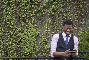 A young man in waistcoat, shirt and tie checking his phone.の写真素材 [FYI02245501]