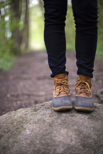 A woman wearing walking boots and jeans, in woodland.の写真素材 [FYI02245520]