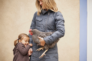 A woman holding a chicken under one arm. A young girl.の写真素材 [FYI02245560]