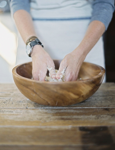 A cook preparing pastry, mixing it by hand on a tabletop.の写真素材 [FYI02245573]