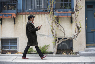 A woman in a warm coat walking, checking her phone.の写真素材 [FYI02245607]