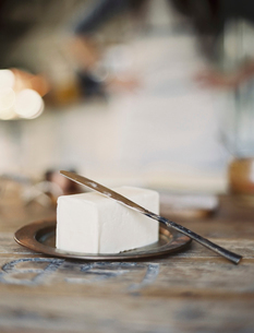 A slab of fresh organic butter, on a wooden dish.の写真素材 [FYI02245639]
