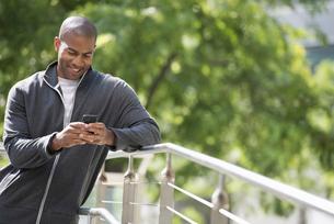 City park. A man in a sweatshirt, using his smart phone.の写真素材 [FYI02245722]